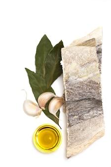 Morue sèche avec de l'huile sur une surface blanche