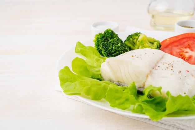 Morue à la vapeur. paléo, céto, fodmap alimentation saine avec des légumes sur une plaque blanche