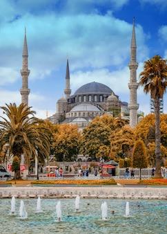 Mosquée bleue au loin sur la place sultanahmet avec une fontaine au premier plan.