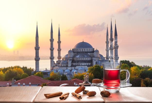 La mosquée bleue et le thé d'istanbul avec des bâtons de cannelle et des dattes, turquie.