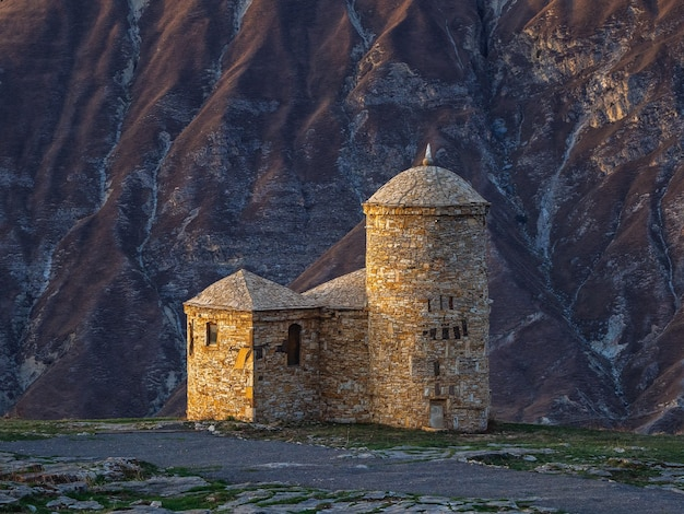 Mosquée de pierre sur fond de montagnes. la lumière du soir brille magnifiquement sur la vieille mosquée en pierre. hunza. daghestan.