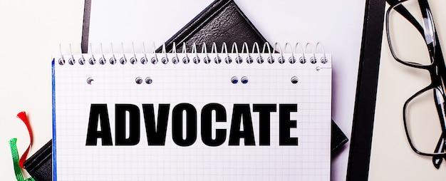 Le mot advocate est écrit en rouge dans un cahier blanc à côté de lunettes à monture noire