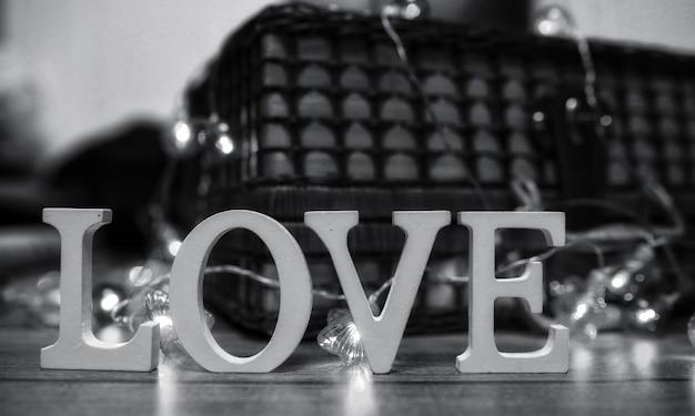 Le mot amour composé de lettres en bois blanches sur fond de bois