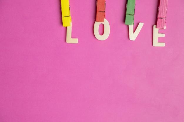 Mot amour dans les coeurs rouges sur fond rose, icône de l'amour, saint valentin, concept de relations