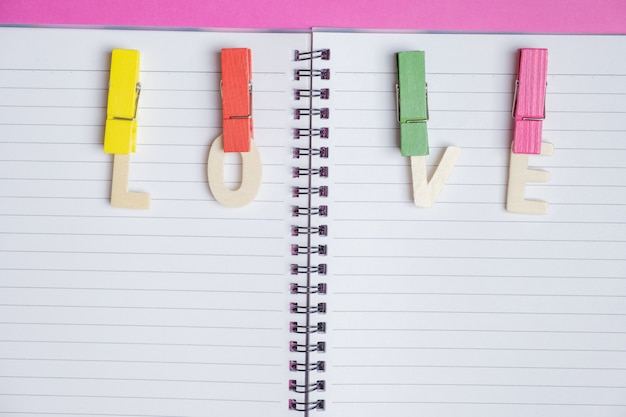 Mot amour dans un livre blanc sur fond rose avec un espace pour le texte