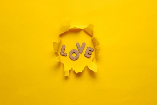 Le mot amour dans un trou déchiré de surface jaune.