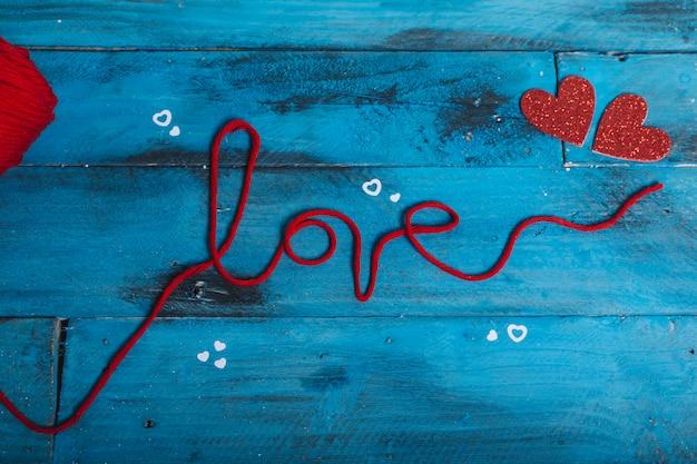 Mot «amour» avec du fil de laine rouge et deux coeurs