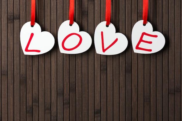 Mot d'amour écrit sur des cartes de voeux en forme de coeur blanc sur le fond en bois.