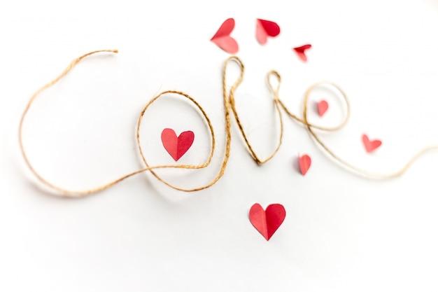 Un mot d'amour écrit avec une corde, des cœurs en papier centrés autour du cœur de papier dans la lettre o