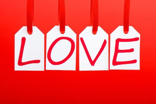Le mot d'amour est écrit dans les balises blanches sur le fond rouge.