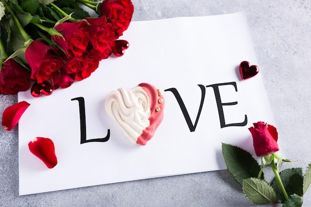 Mot d'amour avec meringue maison en forme de coeur avec des roses rouges. concept de la saint-valentin, espace copie