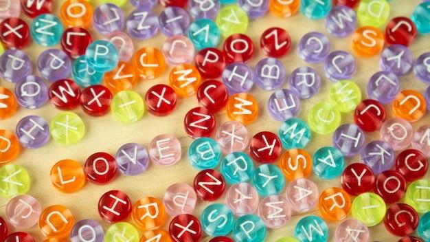 Le mot d'amour sur la perle de l'alphabet multicolore pour le contenu d'arrière-plan