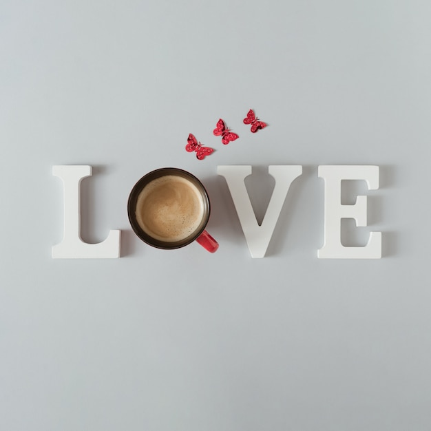 Mot d'amour avec tasse à café et papillons sur table grise.