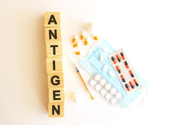 Le mot antigen est composé de cubes en bois sur une surface blanche. concept médical.