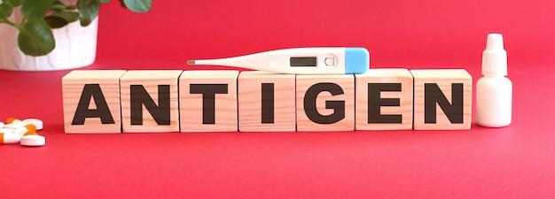 Le mot antigen est fait de cubes en bois sur fond rouge avec des médicaments. concept médical.