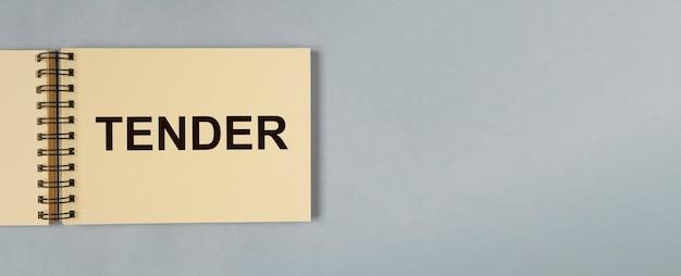 Mot d'appel d'offres sur papier pour ordinateur portable sur fond gris bleu avec espace de copie pour bannière d'entreprise de texte avec ...