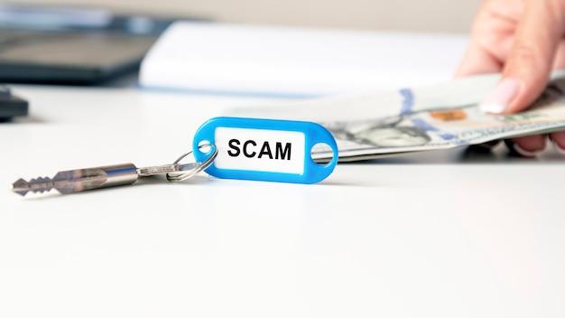 Le mot arnaque est écrit sur un porte-clés bleu. la clé est sur le bureau. à l'arrière-plan, la main d'une femme tient des billets de banque
