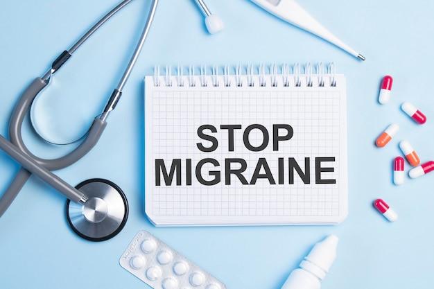 Le mot arrête la migraine écrit sur un bloc-notes blanc sur bleu