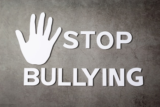 Mot «arrêter l'intimidation» avec signe de la main sur un mur sombre