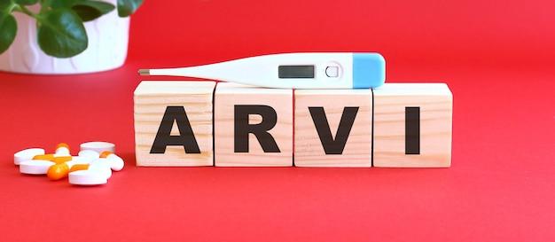 Le mot arvi est composé de cubes en bois sur fond rouge avec des médicaments.