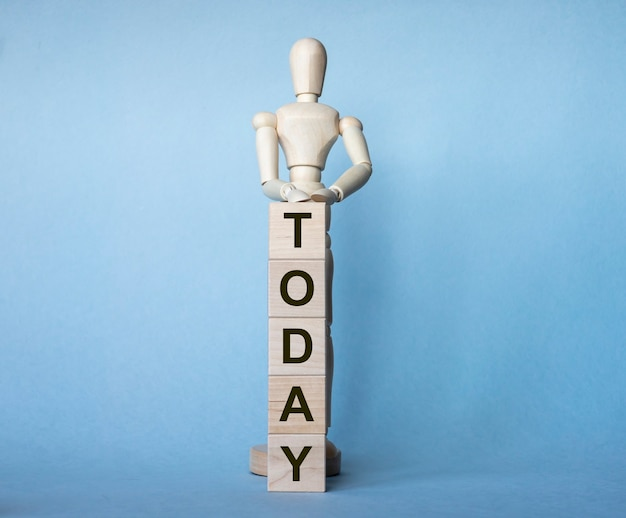Mot aujourd'hui fait de cubes en bois avec figure en bois sur fond bleu