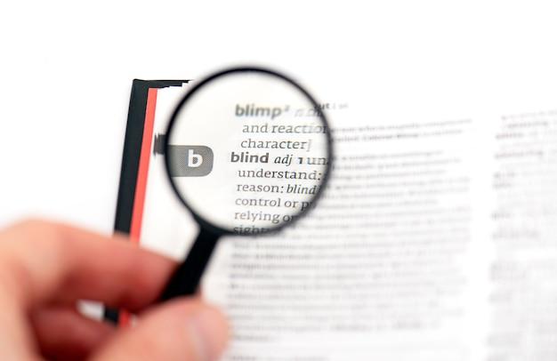 Mot aveugle dans le dictionnaire sous verre magnétique, concept photo