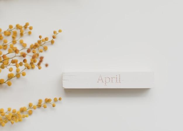 Le mot avril sur cube en bois et fleur de mimosa
