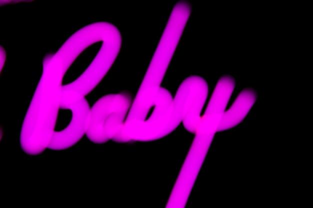 Mot de bébé flou en couleur néon proton violet sur fond noir.