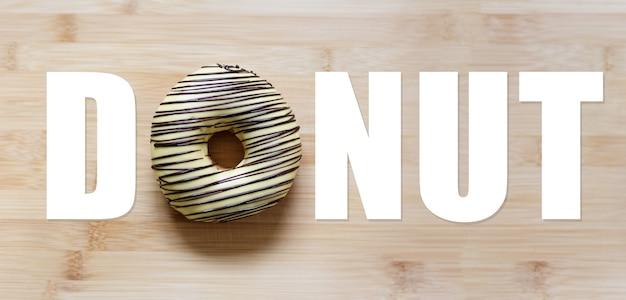 Mot de beignet, avec beignet au lieu de la lettre 'o', sur une table en bois.