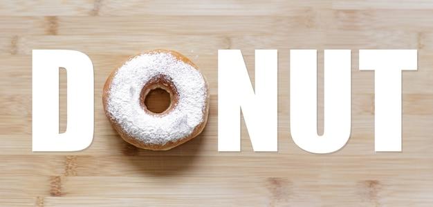 Mot de beignet avec beignet blanc au lieu de la lettre 'o', sur une table en bois.