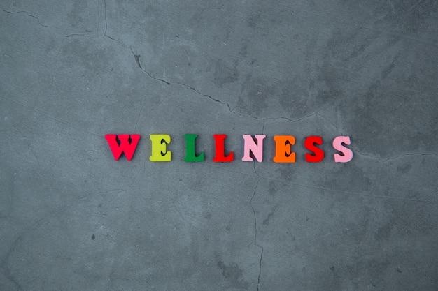 Le mot bien-être multicolore est composé de lettres en bois sur un mur de plâtre gris.