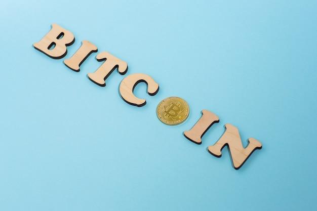 Mot bitcoin composé de lettres en bois et un bitcoin sur surface bleue