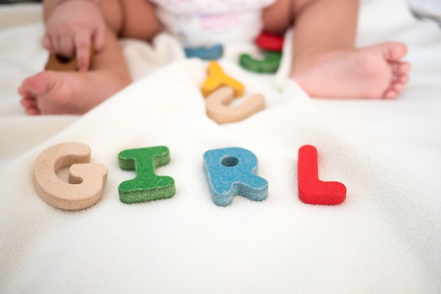 Mot en bois fille texte sur couverture avec pied de l'enfant et copie espace arrière-plan