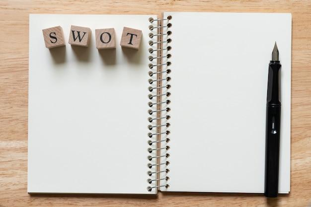 Le mot en bois swot et le stylo plume placés dans le classement du livre (liste).