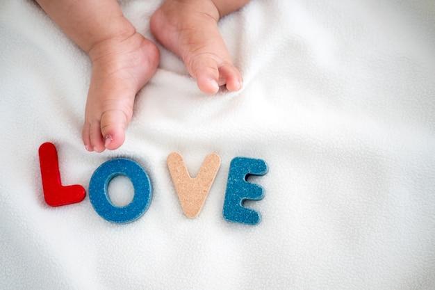 Mot en bois de texte d'amour sur la couverture avec le pied de l'enfant et l'arrière-plan de l'espace copie