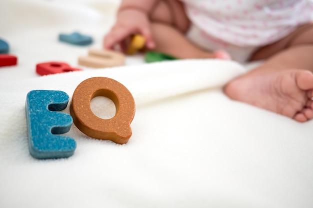 Mot en bois texte eq sur couverture avec pied enfant flou et fond de copie espace
