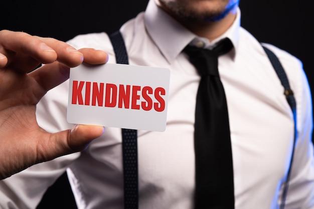 Mot de bonté écrit sur une feuille de papier blanc tenue par un homme.