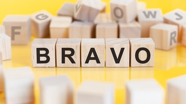 Le mot bravo est écrit sur une structure de cubes en bois. blocs sur un fond clair. notion financière. mise au point sélective