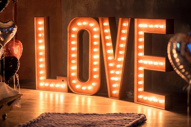 Le mot brillant amour dans un intérieur. d'énormes lettres coûtent l'amour des ampoules sur un sol