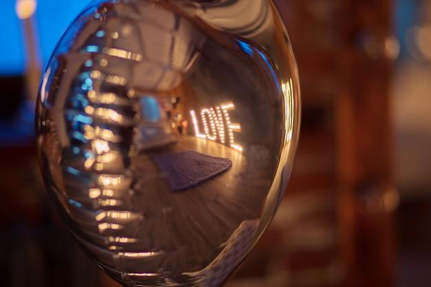 Le mot brillant love est reflété dans le ballon en argent en forme de coeur. la saint valentin. situation intime