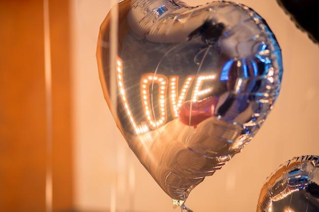 Le mot brillant love est reflété dans le ballon en argent en forme de coeur. la saint valentin