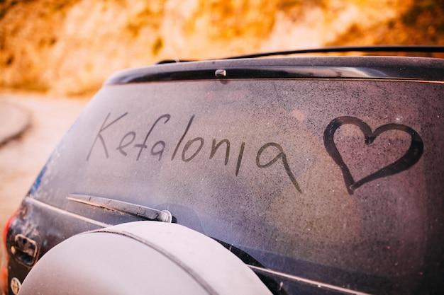 Mot de céphalonie écrit sur une vitre de voiture poussiéreuse