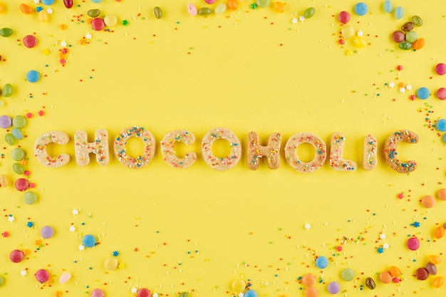 Mot chocolaté fait de biscuits sucrés décorés de paillettes colorées et de bonbons au chocolat autour