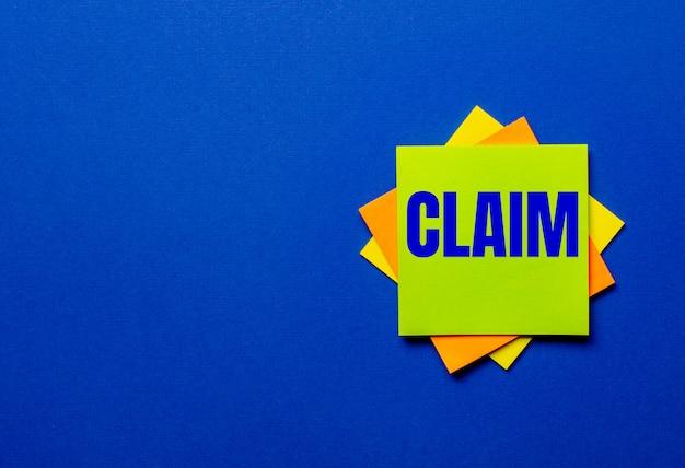 Le mot claim est écrit sur des autocollants brillants sur une surface bleue