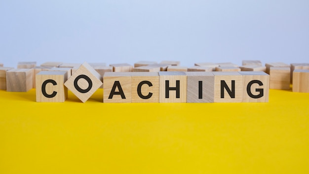 Mot de coaching écrit sur bloc de bois. le mot de réduction est composé de blocs de construction en bois posés sur la table jaune. concept d'entreprise