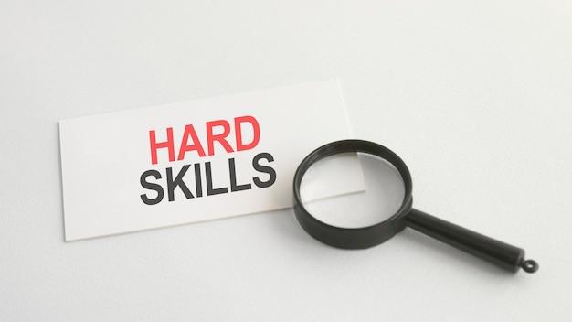 Mot de compétences techniques sur une carte en papier blanc et une loupe