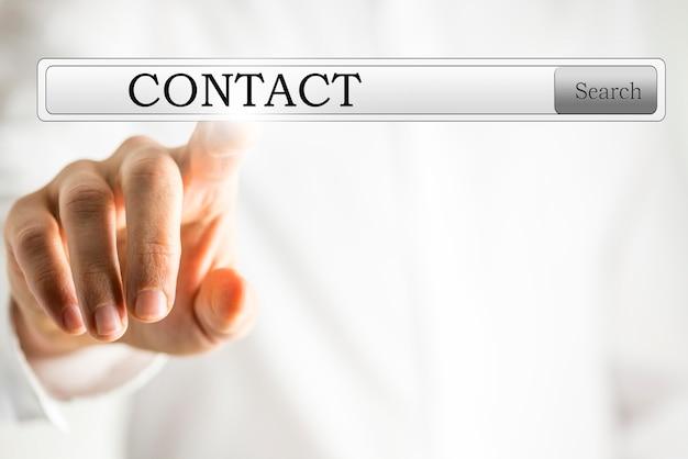 Le mot contact sur une interface virtuelle dans une barre de navigation avec le doigt d'un homme d'affaires sur le point de toucher l'écran pour établir une connexion web