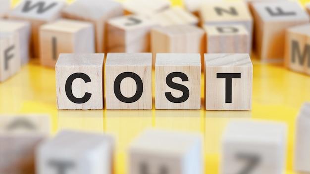 Le mot coût est écrit sur une structure de cubes en bois. blocs sur un fond clair. notion financière. mise au point sélective.