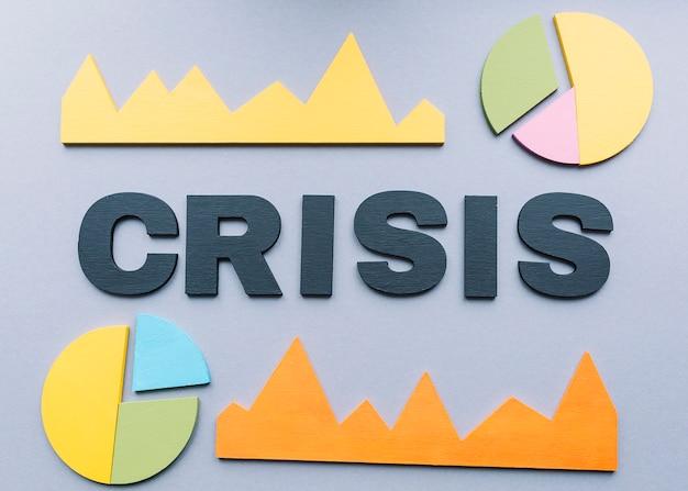 Mot de crise entouré de divers graphique sur fond gris