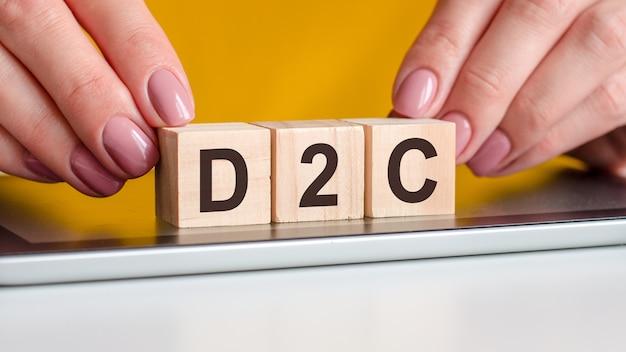 Le mot d2c écrit sur des cubes en bois debout sur un bloc-notes. mise au point sélective. entreprise, éducation, concept financier. d2c - abréviation de direct au consommateur